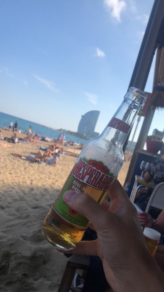 Visit the public beach in Barcelona and have a beer