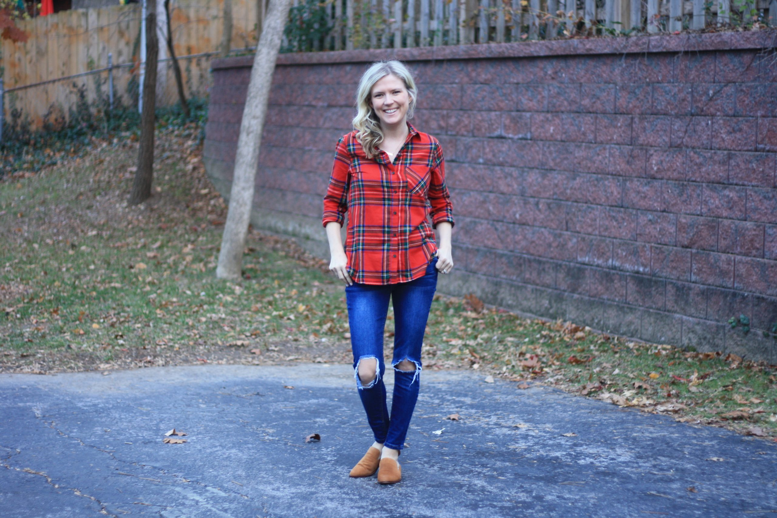 top 3 festive holiday outfits featured by top Missouri fashion blogger, Emmy Lou Styles: image of a blonde woman wearing a red tartan flannel shirt and distressed denim jeans