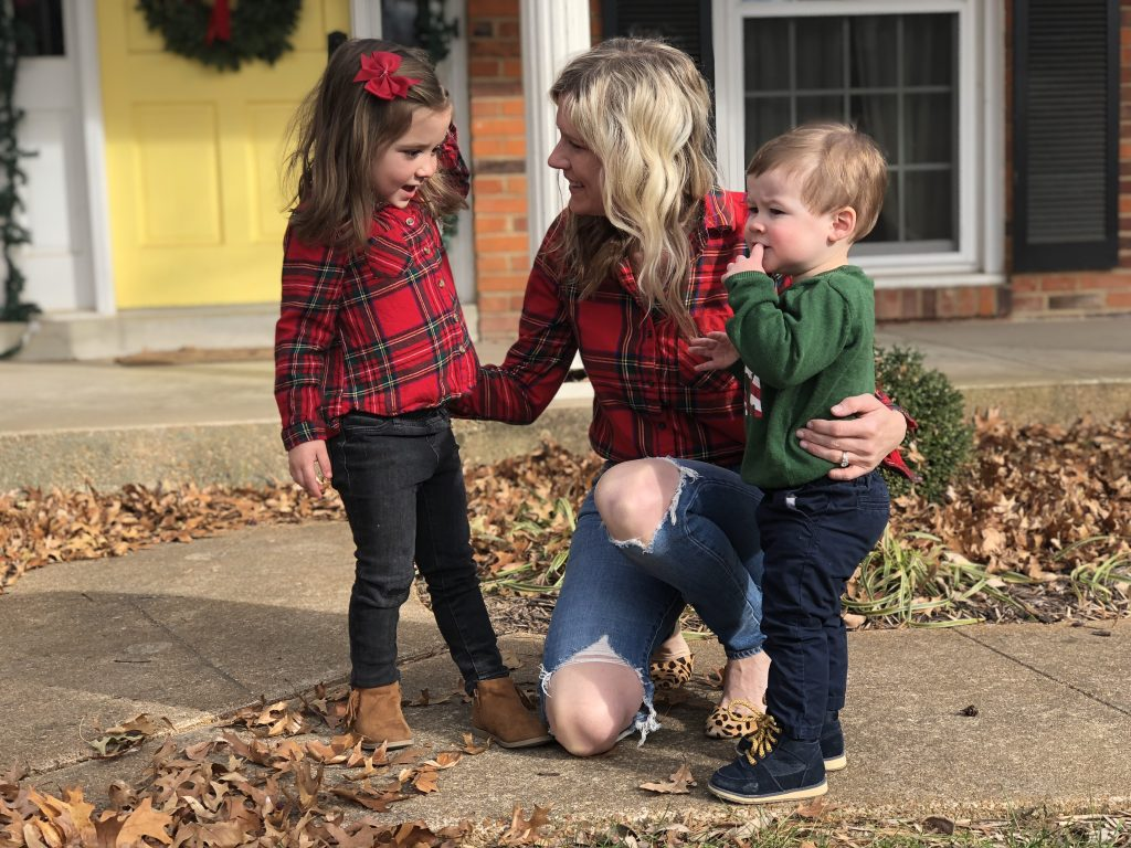 top 3 festive holiday outfits featured by top Missouri fashion blogger, Emmy Lou Styles: image of a blonde woman wearing a red tartan flannel shirt and distressed denim jeans and a toddler wearing a red tartan flannel shirt