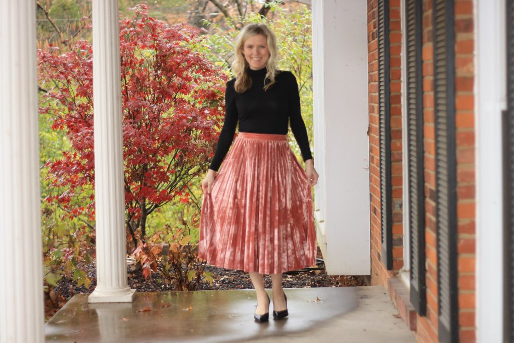 top 3 festive holiday outfits featured by top Missouri fashion blogger, Emmy Lou Styles: image of a blonde woman wearing a red velvet skirt and black turtleneck