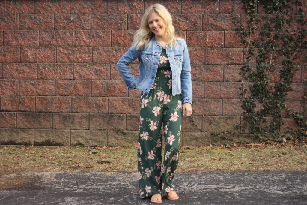 women's floral jumpsuit and denim jacket  | 3 Jumpsuit styling tips featured by top US fashion blogger, Emmy Lou Styles: image of a blonde woman wearing a floral off the shoulder jumpsuit and a denim jacket