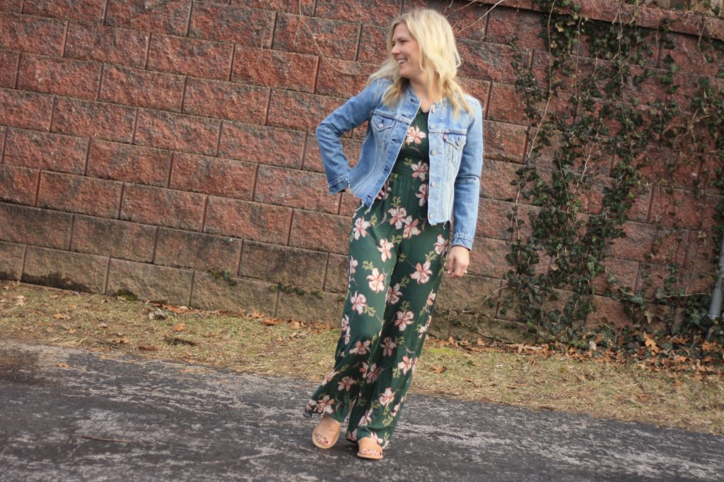 women's denim jacket worn over jumpsuit  | 3 Jumpsuit styling tips featured by top US fashion blogger, Emmy Lou Styles: image of a blonde woman wearing a floral off the shoulder jumpsuit and a denim jacket