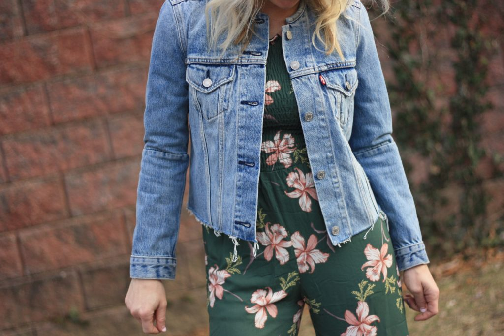 womens denim jacket over a jumpsuit | 3 Jumpsuit styling tips featured by top US fashion blogger, Emmy Lou Styles: image of a blonde woman wearing a floral off the shoulder jumpsuit and a denim jacket
