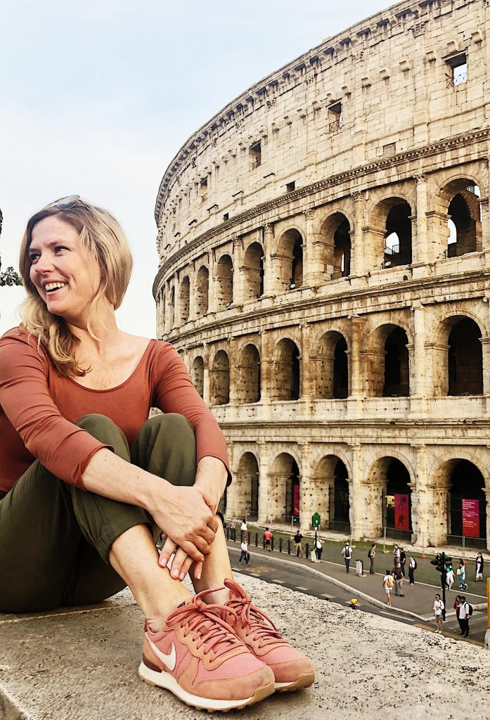 Emily from Emmy Lou Styles poses in front of the Colosseum in Rome, Italy