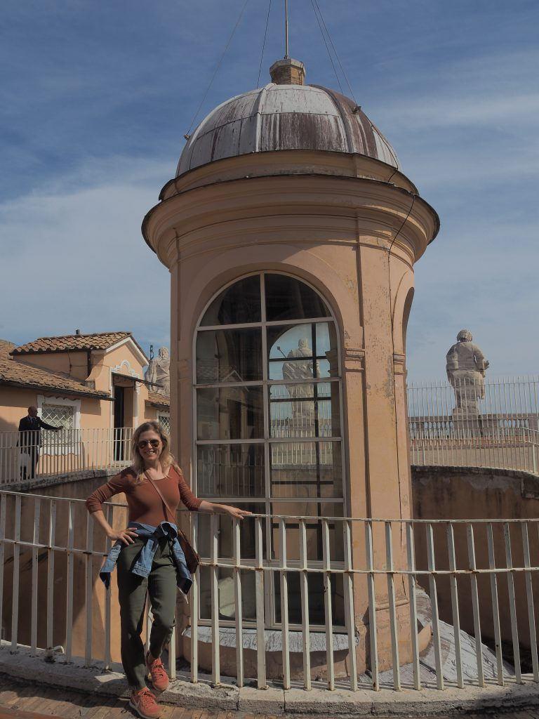 Emily from Emmy Lou Styles poses next to the bell tower at St. Peter's Basilica
