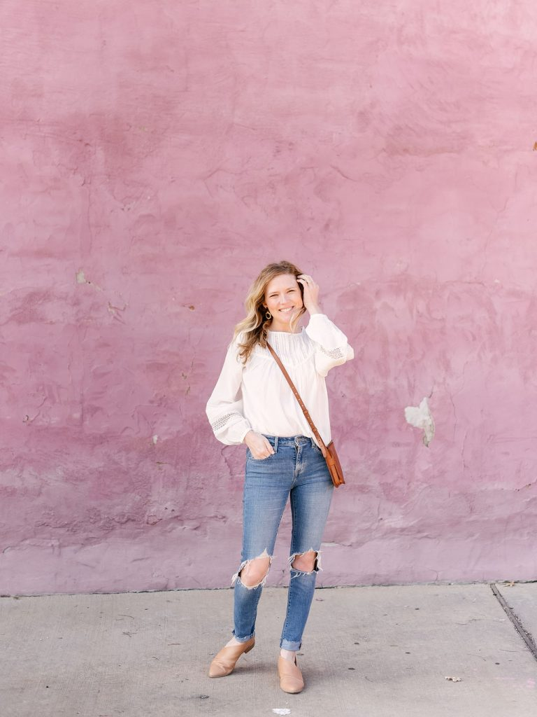 Emily from Emmy Lou Styles shares how she styles a feminine white blouse with busted knee jeans for a casual spring look.