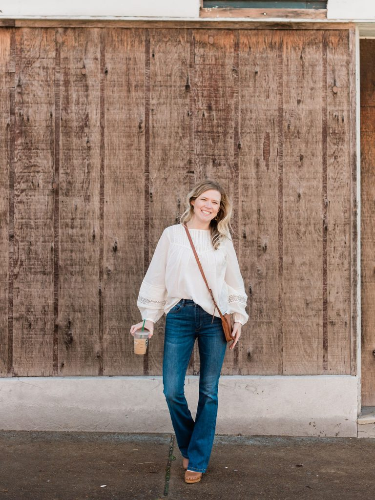 Emily from Emmy Lou Styles shares how she styles a white feminine blouse with high waisted flared jeans.