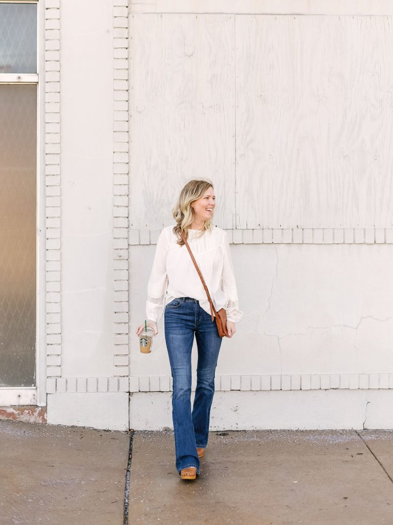 Emily from Emmy Lou Styles in Saint Louis Missouri shares how she styles a feminine white shirt with hight waist flared jeans.