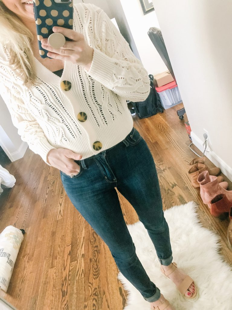 H&M Cropped Cableknit sweater with large buttons. Image of woman standing in front of mirror taking photo.