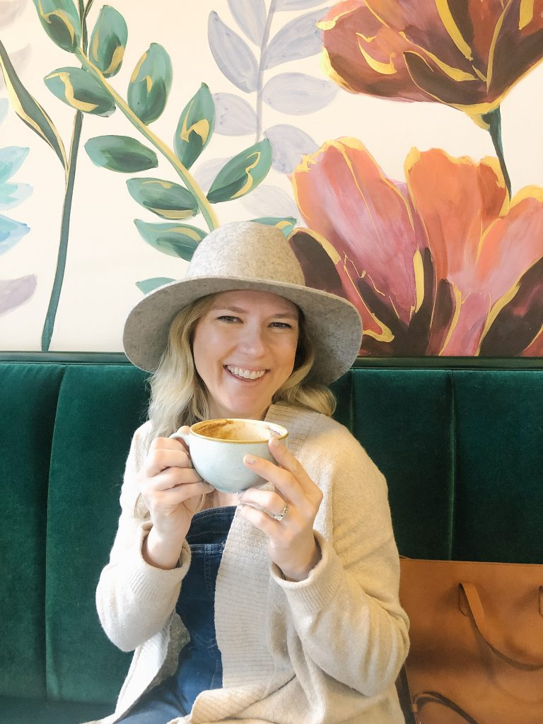 How I quit my corporate job and transitioned. Image of a girl sitting in front of floral wallpaper wall drinking a latte.
