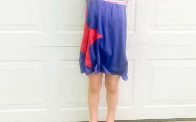 30 Patriotic Outfits for Kids; little girl wearing blue dress with patriotic red star on it and star sunglasses