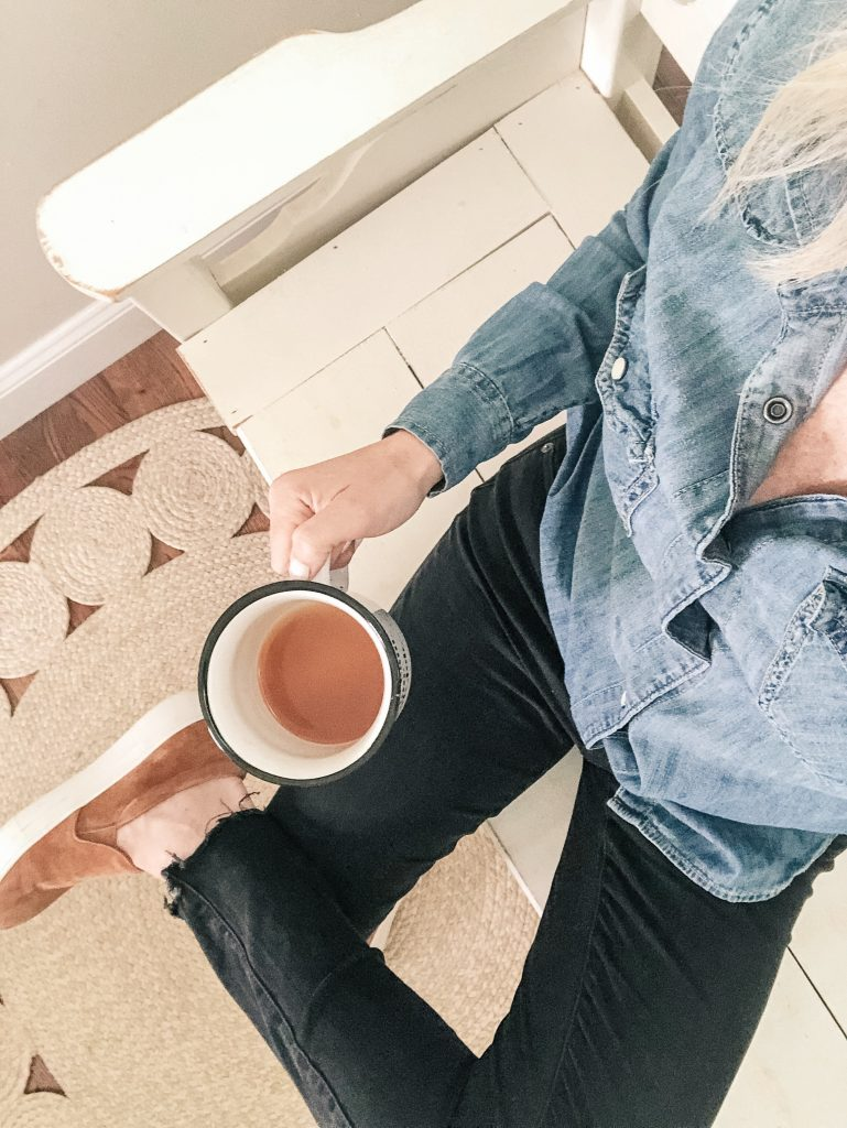 girl sitting holding coffee cup wearing chambray shirt and black denim