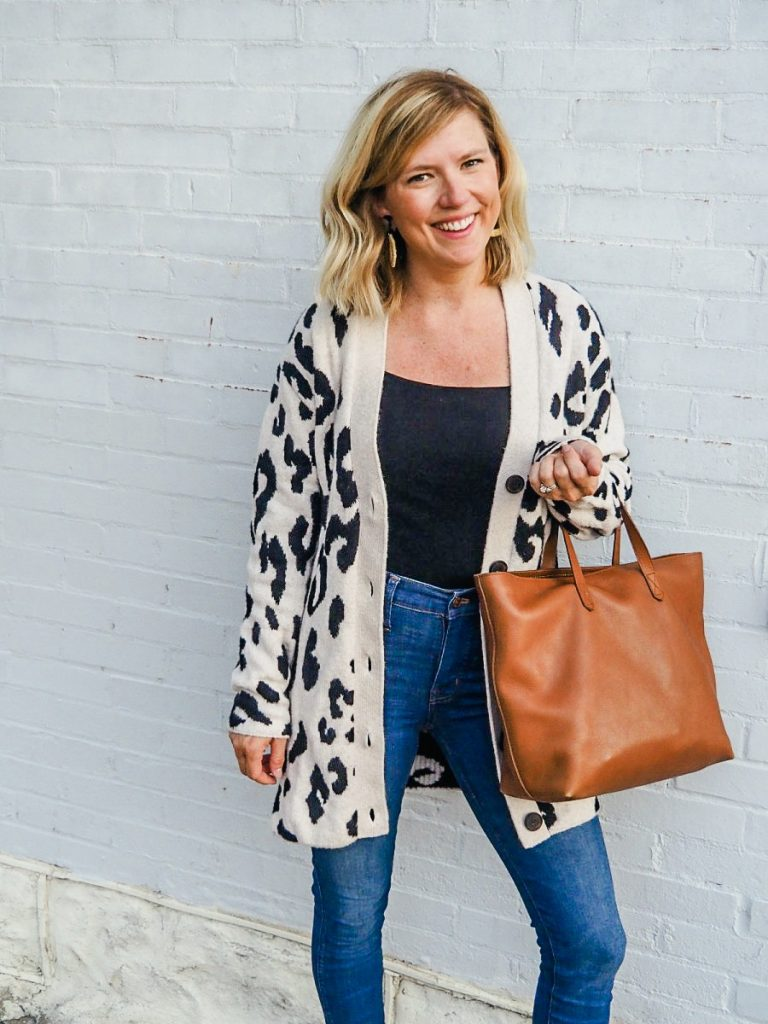 Woman standing wearing a long leopard cardigan