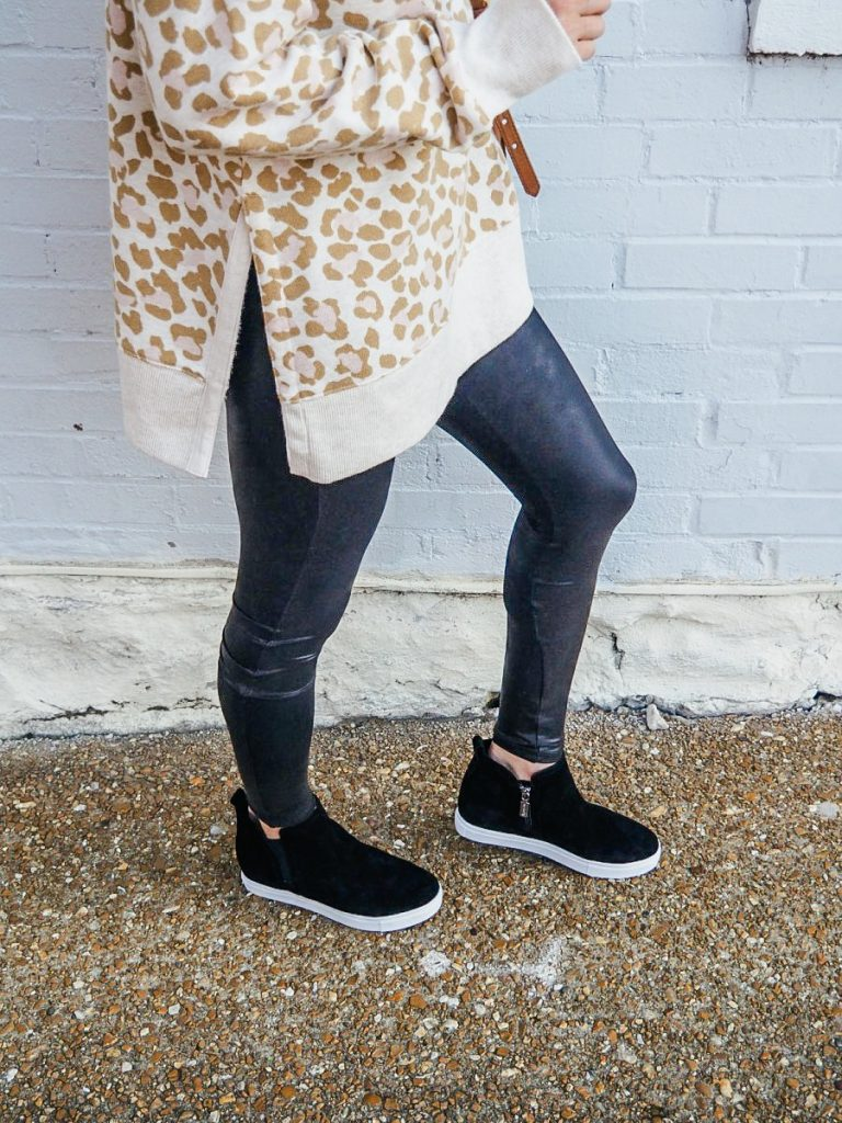 Woman wearing black sneaker booties