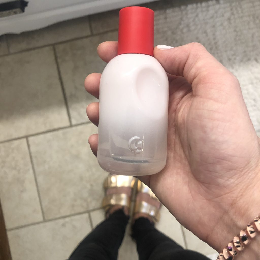 Woman holding a bottle of Glossier perfume