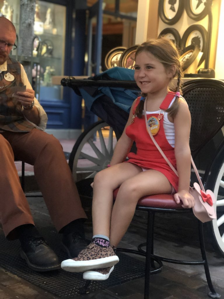 Girl sitting having silhouette done at Disney World