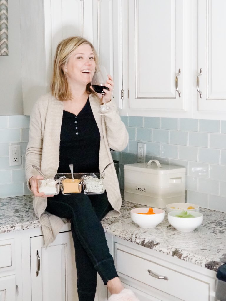 Woman sitting on counter drinking wine and holding appetizers