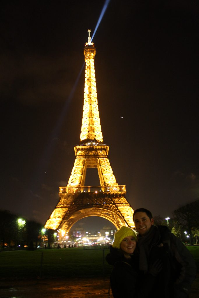 Couple posing in front of Eiffel Tower at night