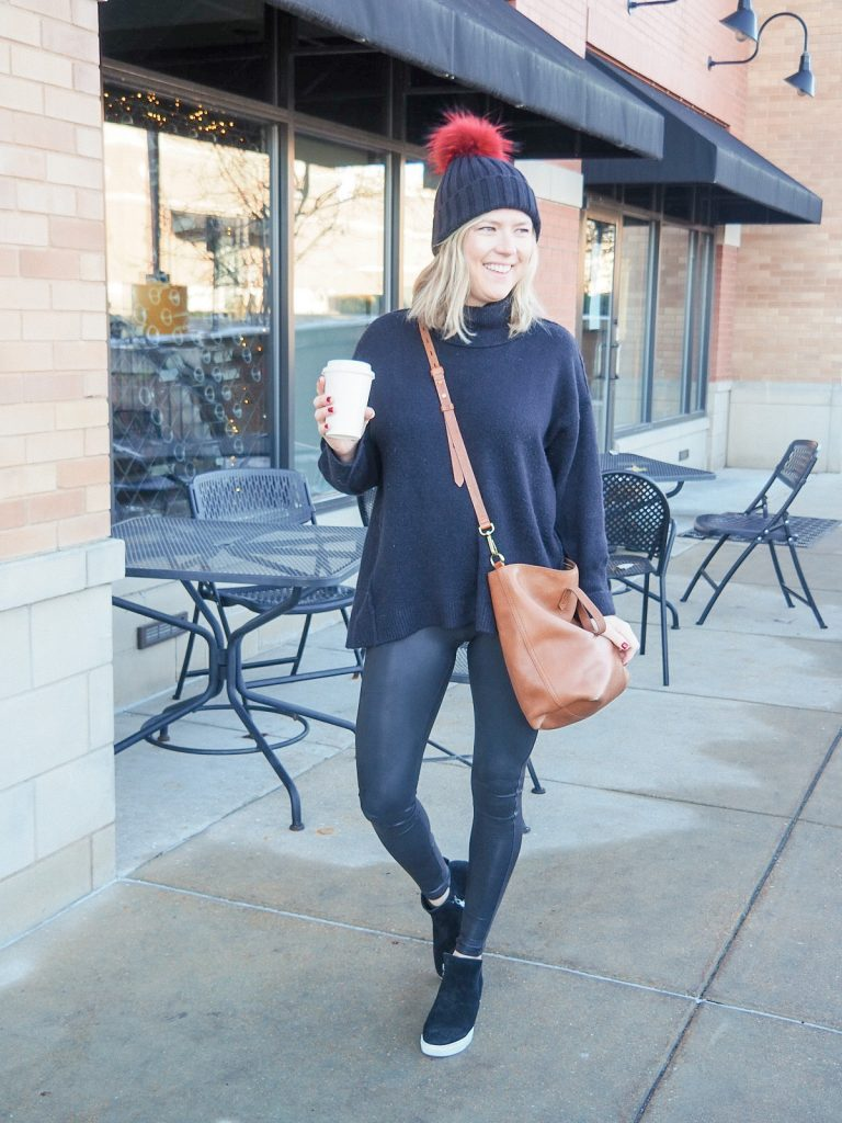 Woman wearing black faux leather Spanx leggings with Free People black oversized sweater