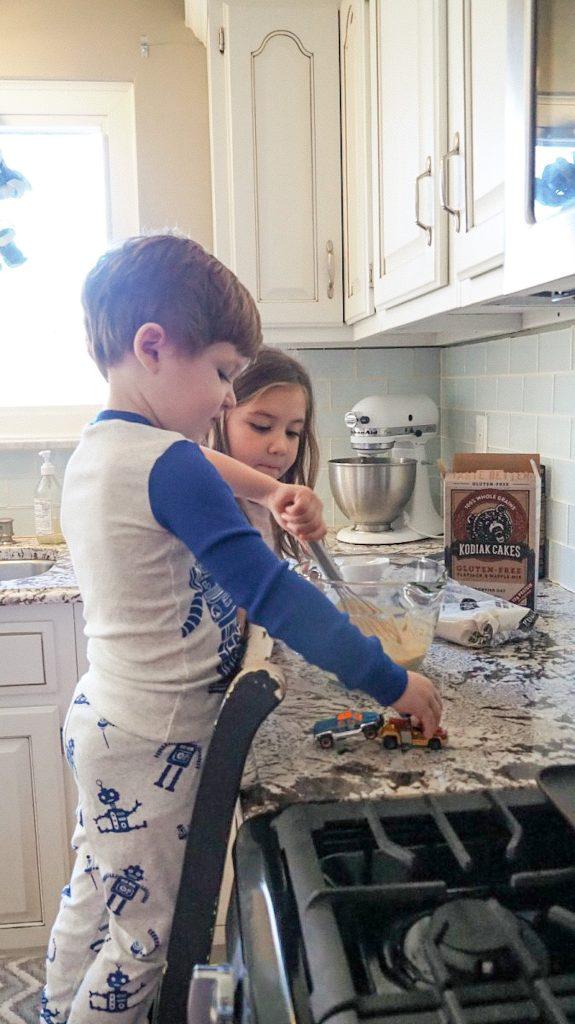 Kids helping to make Kodiak Cake pancakes in a white kitchen