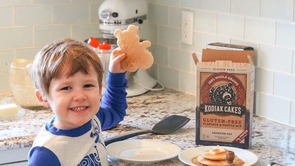 Boy holding up teddy bear shaped pancake made from Kodiak Cakes pancakes