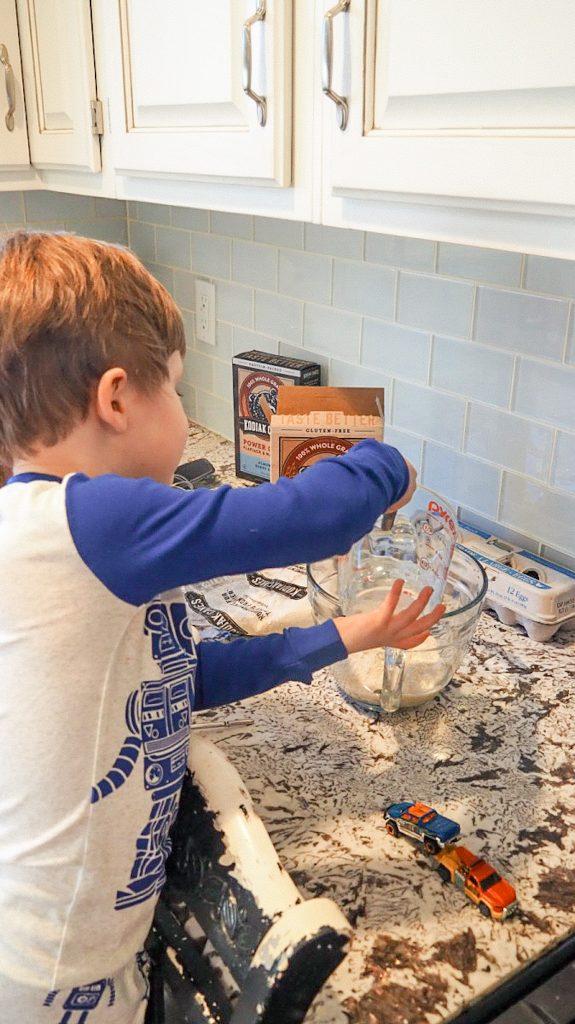 Toddler boy pouring ingredients into bowl for making pancakes