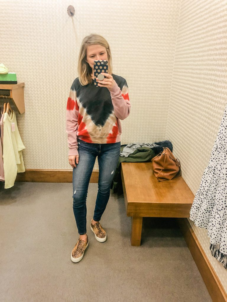 Woman standing in front of mirror at Evereve wearing tie dye sweatshirt