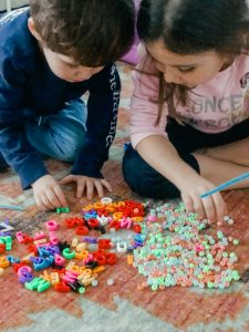 Kids making pony bead bracelets on the floor