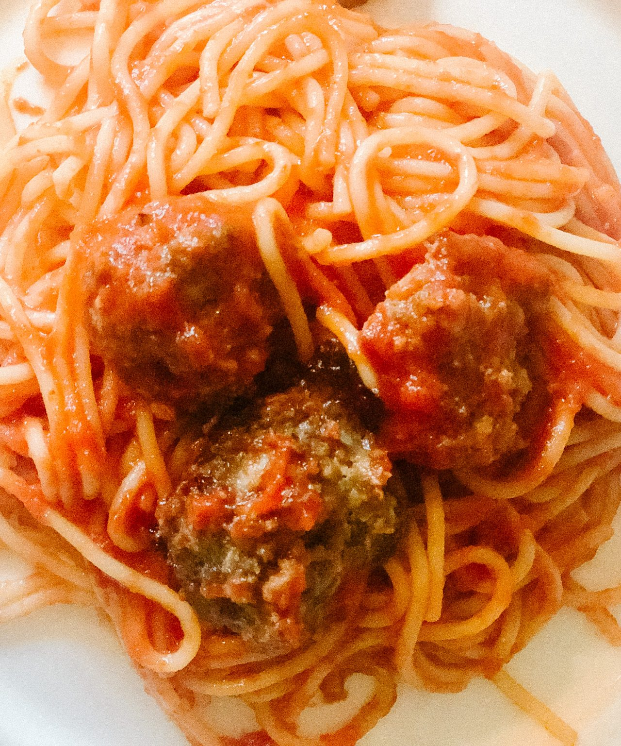 Homemade beef meatballs sitting on top of spaghetti