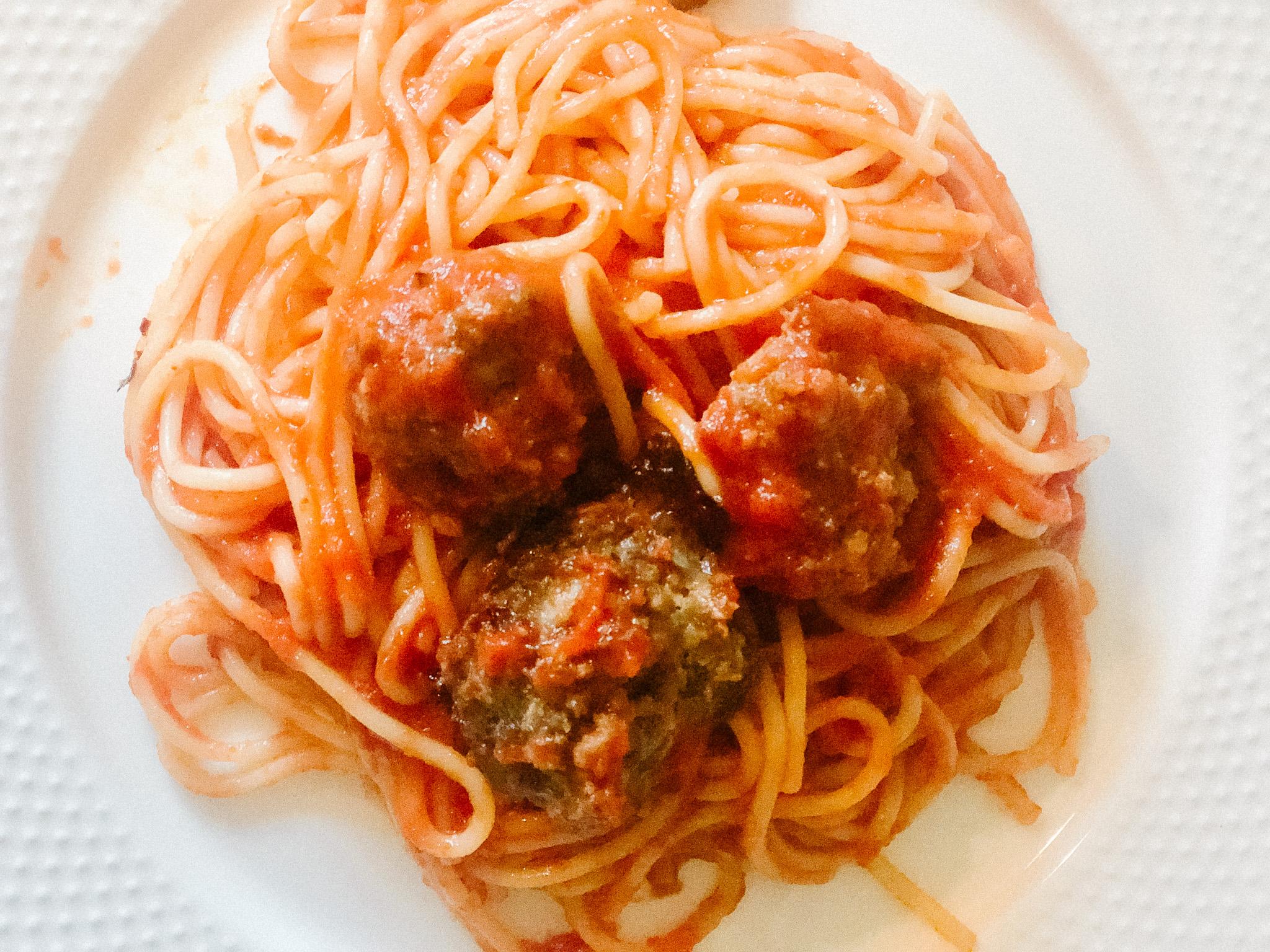 Homemade beef meatballs sitting on top of spaghetti