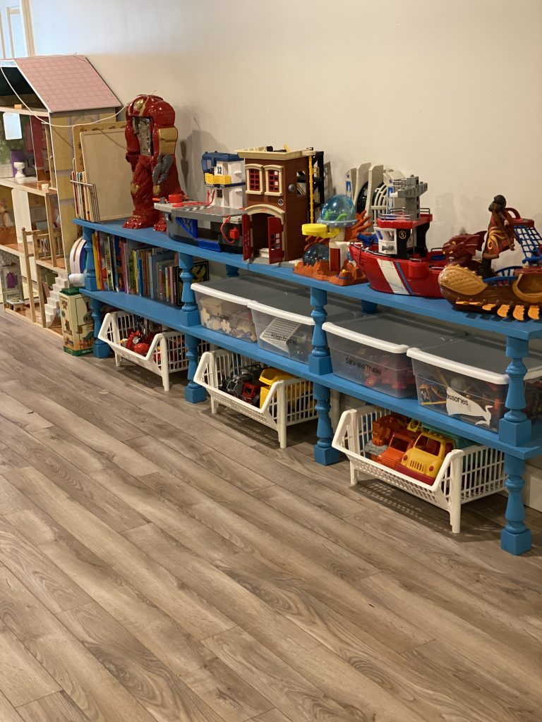 Organized kids playroom with long shelf