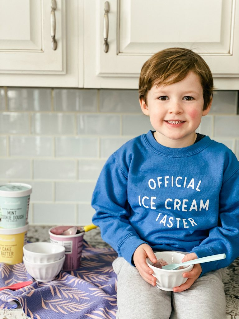 Little boy holding bowl of ice cream