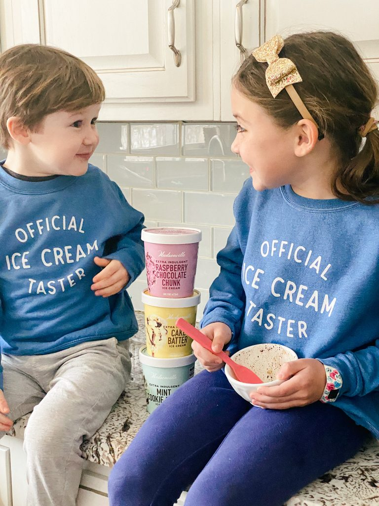 two kids enjoying Hudsonville ice cream in the kitchen