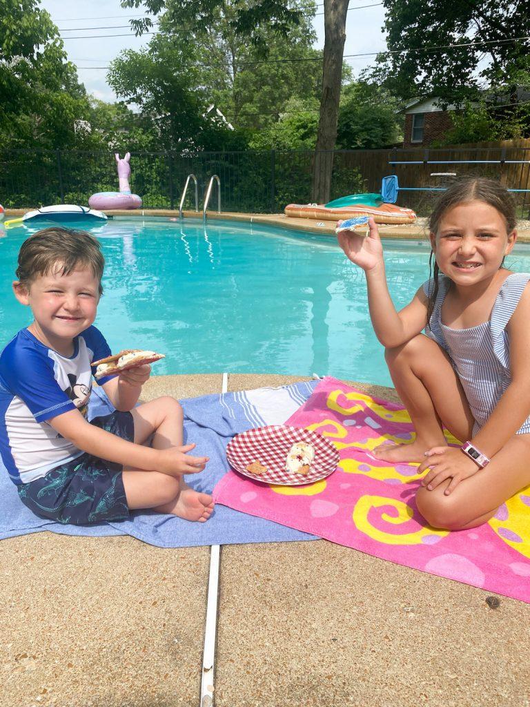 Kids enjoying ice cream sandwiches by a pool